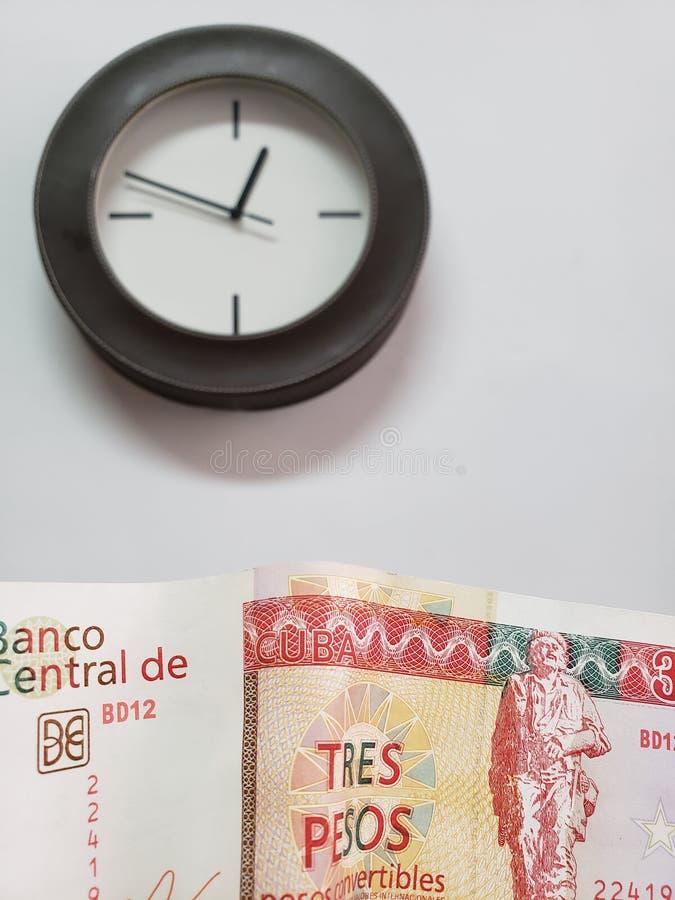 προσέγγιση στο κουβανικό τραπεζογραμμάτιο και υπόβαθρο με ένα κυκλικό ρολόι τοίχων στοκ εικόνες
