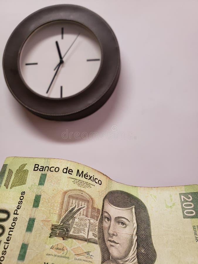 προσέγγιση στο μεξικάνικο τραπεζογραμμάτιο 200 πέσων και του υποβάθρου με ένα κυκλικό ρολόι τοίχων στοκ φωτογραφία