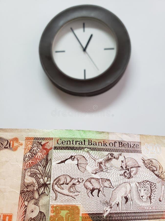 προσέγγιση στο μπελιζινό τραπεζογραμμάτιο είκοσι δολαρίων και υποβάθρου με ένα κυκλικό ρολόι τοίχων στοκ εικόνες με δικαίωμα ελεύθερης χρήσης