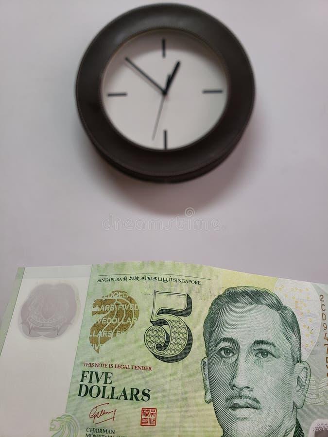 προσέγγιση στο σιγκαπούριος τραπεζογραμμάτιο πέντε δολαρίων και υποβάθρου με ένα κυκλικό ρολόι τοίχων στοκ εικόνες
