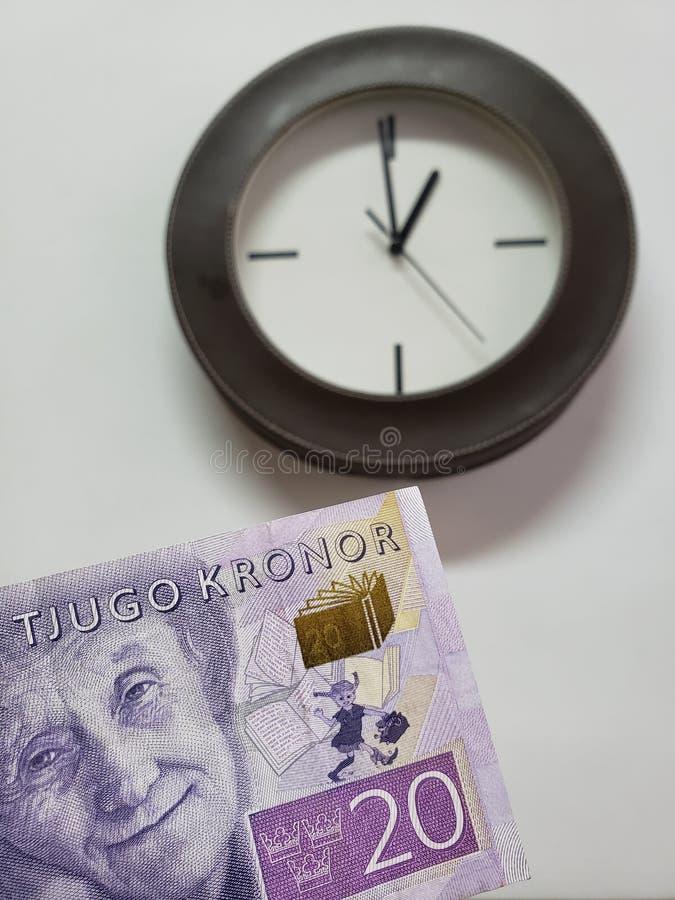 προσέγγιση στο σουηδικό τραπεζογραμμάτιο του kronor είκοσι και του υποβάθρου με ένα κυκλικό ρολόι τοίχων στοκ φωτογραφίες με δικαίωμα ελεύθερης χρήσης