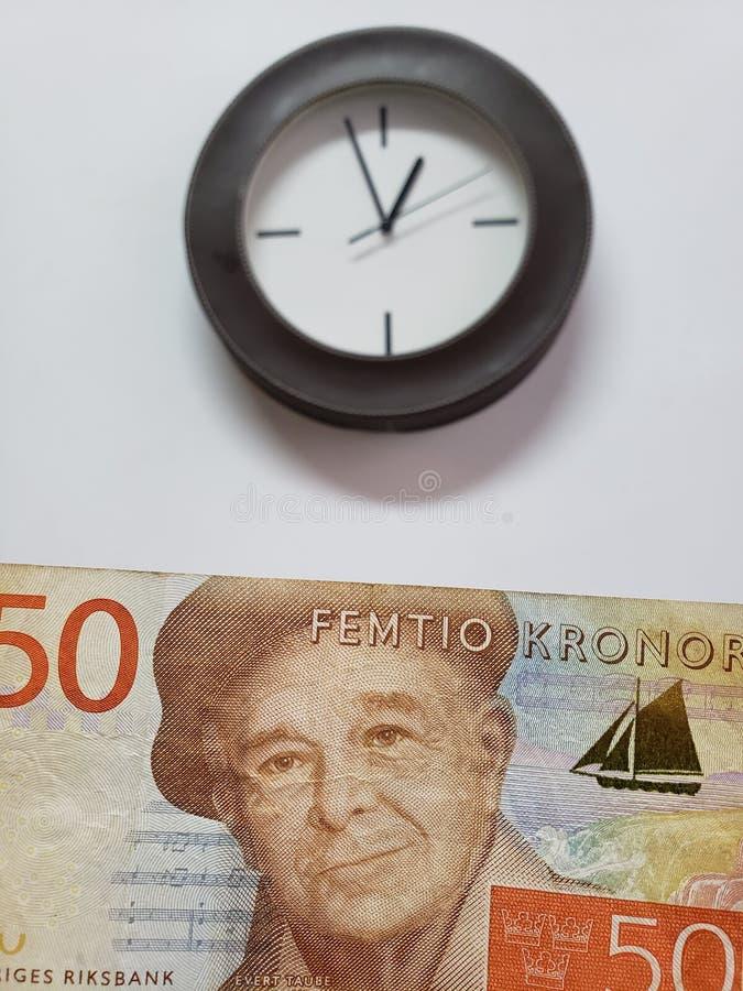 προσέγγιση στο σουηδικό τραπεζογραμμάτιο του kronor πενήντα και του υποβάθρου με ένα κυκλικό ρολόι τοίχων στοκ φωτογραφίες με δικαίωμα ελεύθερης χρήσης