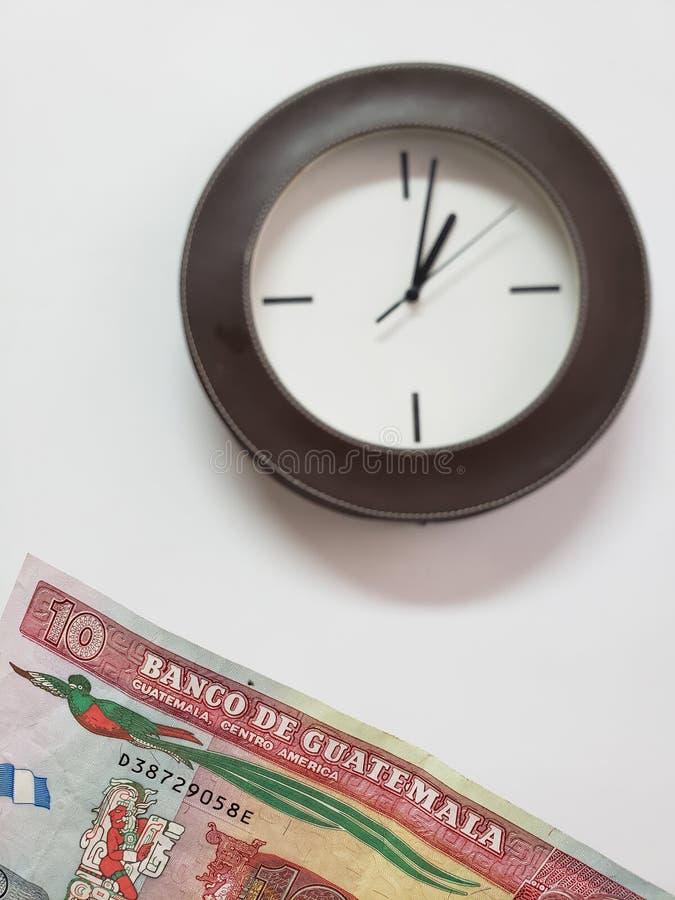 προσέγγιση στο της Γουατεμάλας τραπεζογραμμάτιο δέκα quetzales και υποβάθρου με ένα κυκλικό ρολόι τοίχων στοκ φωτογραφία με δικαίωμα ελεύθερης χρήσης