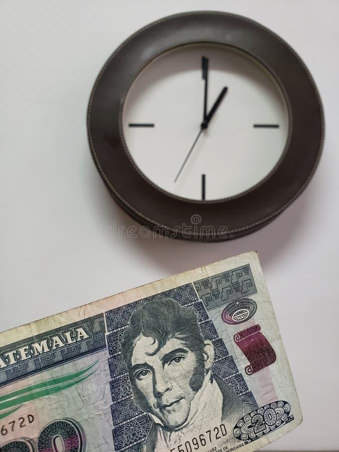 προσέγγιση στο της Γουατεμάλας τραπεζογραμμάτιο είκοσι quetzales και υποβάθρου με ένα κυκλικό ρολόι τοίχων στοκ φωτογραφίες με δικαίωμα ελεύθερης χρήσης