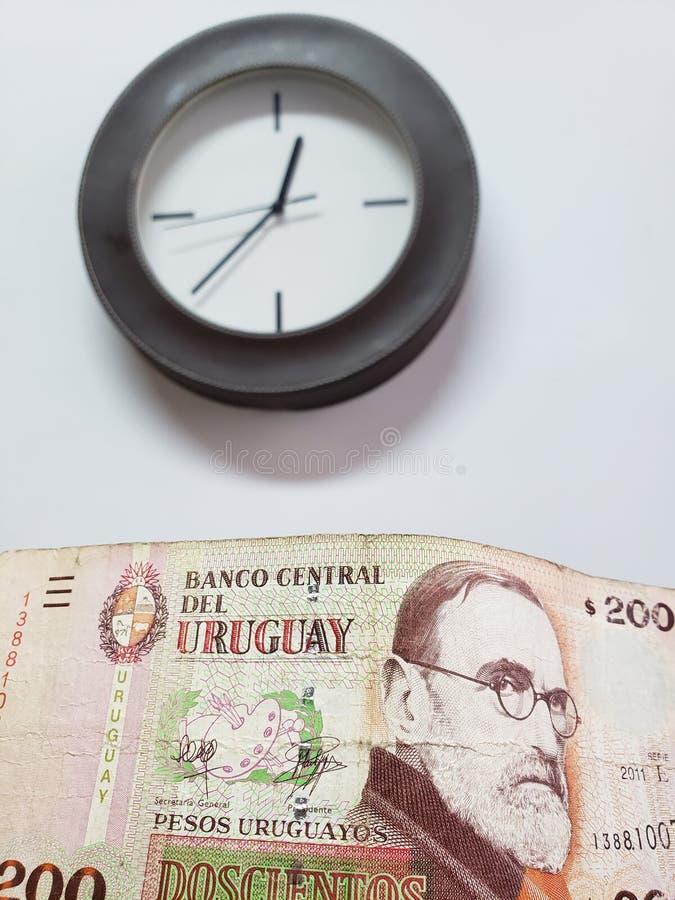 προσέγγιση στο τραπεζογραμμάτιο Ουρουγουανών 200 πέσων και του υποβάθρου με ένα κυκλικό ρολόι τοίχων στοκ εικόνες