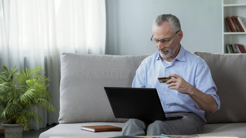 Προσεκτική ανώτερη συνεδρίαση ατόμων στον καναπέ και παρεμβολή του αριθμού καρτών στο lap-top στοκ εικόνες με δικαίωμα ελεύθερης χρήσης