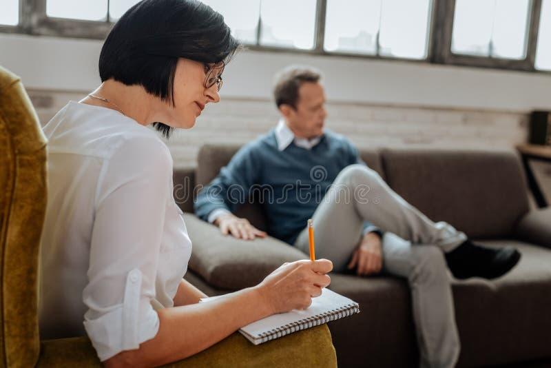 Προσεκτική σκοτεινός-μαλλιαρή γυναίκα στην άσπρη μπλούζα που γράφει κάτω τις πληροφορίες στοκ εικόνες
