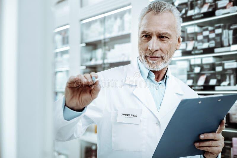 Προσεκτικός ανώτερος φαρμακοποιός που εργάζεται συνειδητά στο φαρμακείο στοκ φωτογραφίες