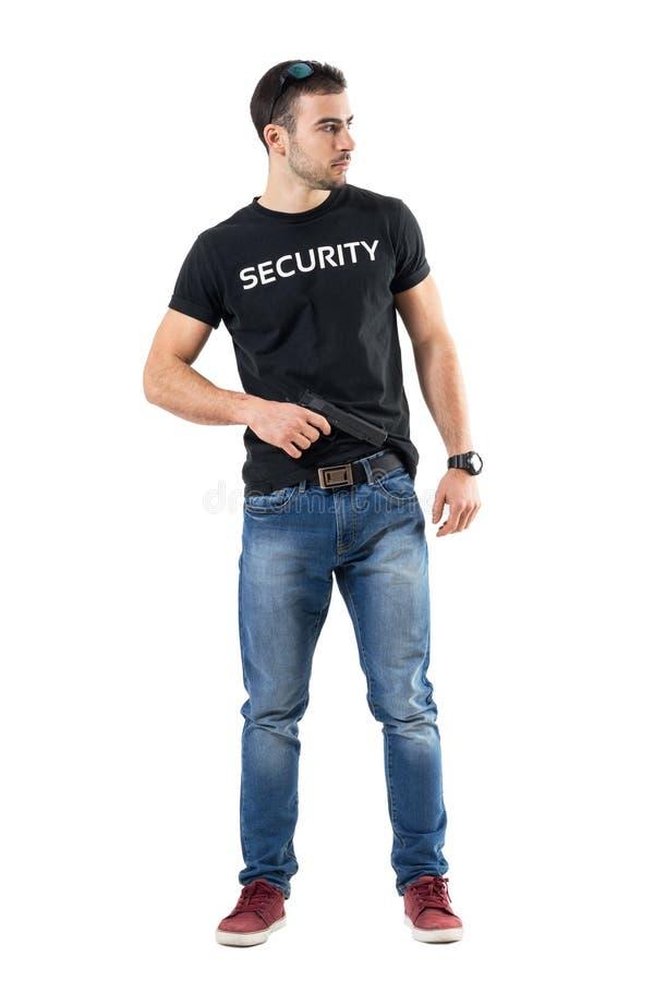 Προσεκτικός μυστικός αξιωματούχος που παίρνει το πυροβόλο όπλο που συνδέεται στη ζώνη που κοιτάζει μακριά στοκ εικόνες