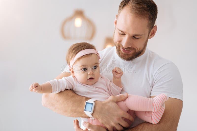Προσεκτικός νέος πατέρας που κρατά νεογέννητό του στο σπίτι στοκ φωτογραφίες
