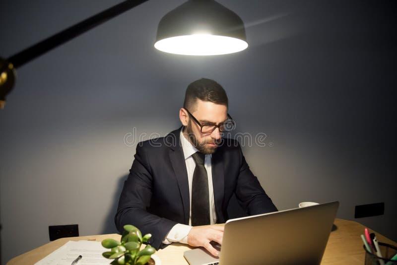 Προσεκτικό άτομο που εργάζεται στο lap-top αργά τη νύχτα στοκ εικόνα
