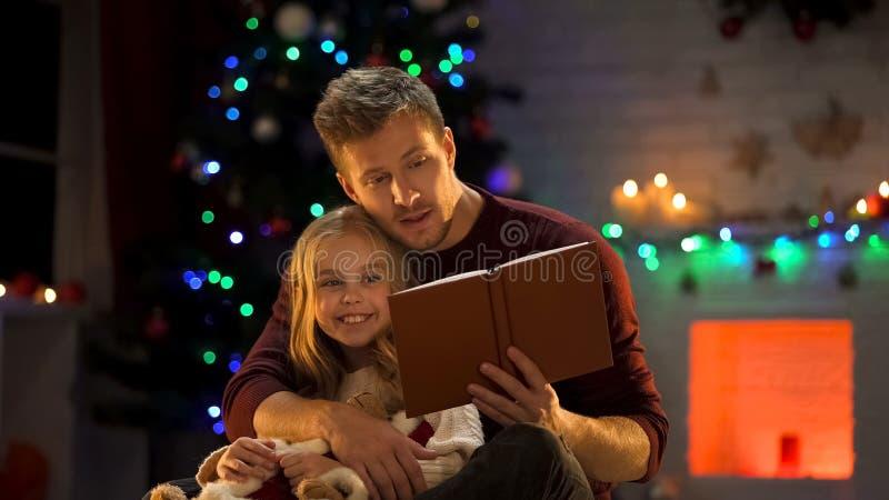 Προσεκτικό παραμύθι Χριστουγέννων ανάγνωσης πατέρων για το ευτυχές διακοσμημένη κοριτσιών πλησίον δέντρο στοκ εικόνα με δικαίωμα ελεύθερης χρήσης