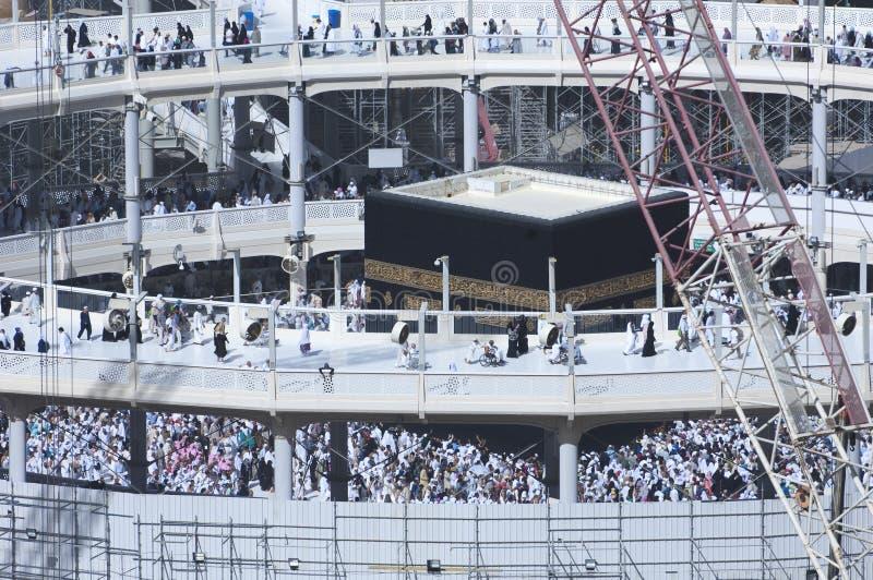 Προσκυνητές Tawaf γύρω από Al-Kaaba ενώ οι οικοδομές είναι Goin στοκ εικόνα με δικαίωμα ελεύθερης χρήσης