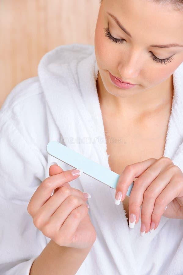 Προσοχή γυναικών της χρησιμοποίησης νυχιών της nailfile στοκ εικόνα με δικαίωμα ελεύθερης χρήσης