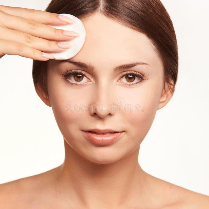 Προσοχή εγχώριου προσώπου Το κορίτσι αφαιρεί makeup Χέρι γυναικών με το μαξιλάρι Δέρμα καθαρό με το βαμβάκι στοκ εικόνες