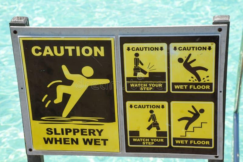 Προσοχή ολισθηρή όταν υγρό κίτρινο σημάδι κοντά στα σκαλοπάτια στον ωκεανό στοκ εικόνες