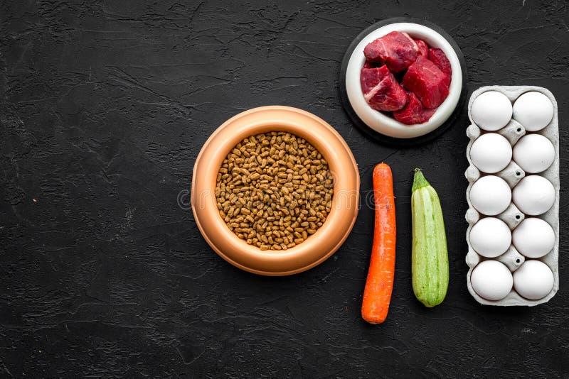 Προσοχή της Pet με τα ξηρά τρόφιμα, τα λαχανικά και το ακατέργαστο κρέας για το σκυλί ή τη γάτα στο πλαστικό κύπελλο στο μαύρο δι στοκ εικόνα