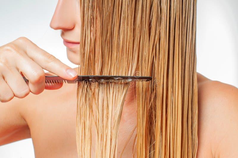 Προσοχή τριχώματος Η όμορφη γυναίκα βουρτσίζει την υγρή ξανθή τρίχα της στοκ φωτογραφίες