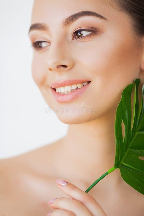 Προσοχή SPA Νέα όμορφη γυναίκα brunette με το μεγάλο πράσινο φύλλο στοκ εικόνες