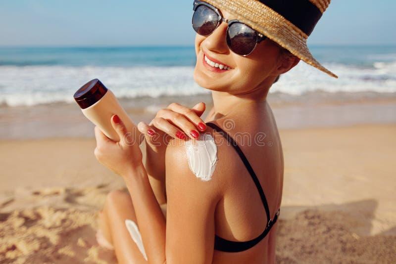 Προστασία ήλιων, κορίτσι που χρησιμοποιεί sunscreen σε ασφαλή αυτή δέρμα υγιές Προκλητική νέα γυναίκα στα μπουκάλια εκμετάλλευσης στοκ φωτογραφίες