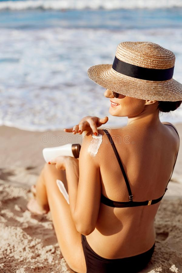 Προστασία ήλιων, κορίτσι που χρησιμοποιεί sunscreen σε ασφαλή αυτή δέρμα υγιές Προκλητική νέα γυναίκα στα μπουκάλια εκμετάλλευσης στοκ εικόνα