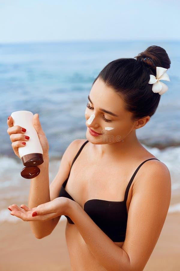 Προστασία ήλιων, κορίτσι που χρησιμοποιεί sunscreen σε ασφαλή αυτή δέρμα υγιές Προκλητική νέα γυναίκα στα μπουκάλια εκμετάλλευσης στοκ εικόνα με δικαίωμα ελεύθερης χρήσης