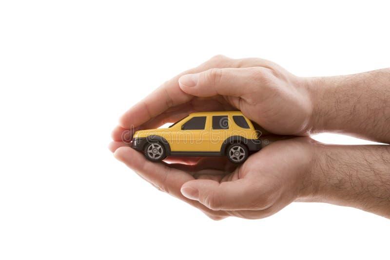 Προστασία αυτοκινήτων Μικρό κίτρινο αυτοκίνητο που καλύπτεται με το χέρι που απομονώνονται στο άσπρο υπόβαθρο στοκ εικόνα με δικαίωμα ελεύθερης χρήσης