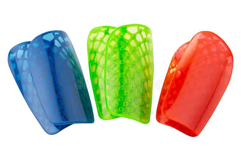 Προστασία ποδιών, για το παιχνίδι του ποδοσφαίρου, τρία ζευγάρια, που χρωματίζονται, σε ένα άσπρο υπόβαθρο στοκ εικόνες
