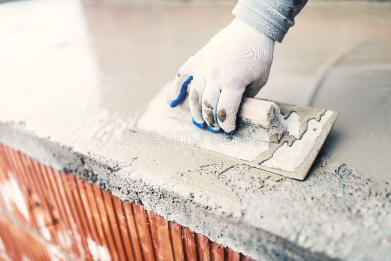 Προστατευτικό υλικό ενάντια στο νερό στην οικοδόμηση στεγανοποιώντας τσιμέντο εργαζομένων στοκ εικόνα