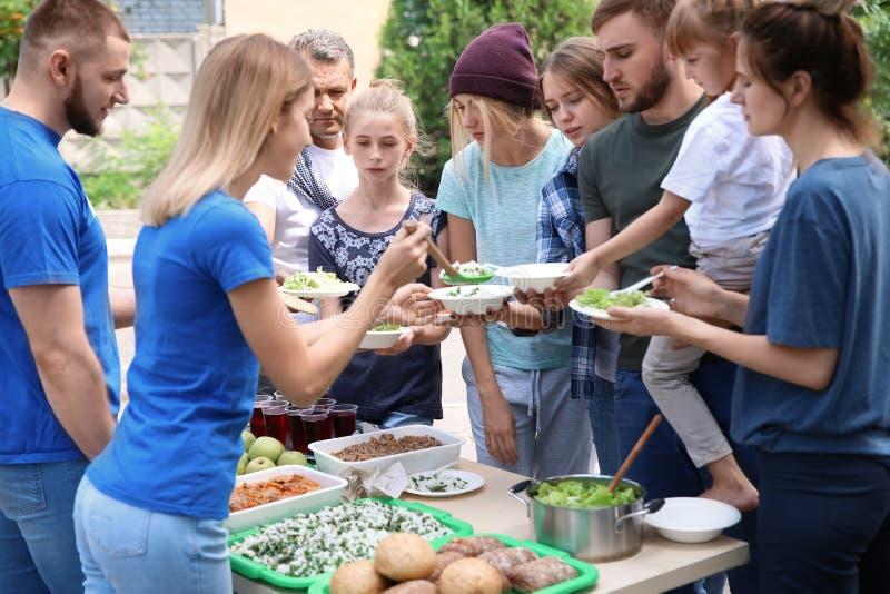 Προσφέρεται εθελοντικά τα εξυπηρετώντας τρόφιμα για τους φτωχούς ανθρώπους στοκ εικόνα με δικαίωμα ελεύθερης χρήσης