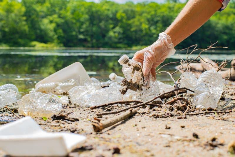 Προσφέρεται εθελοντικά τα καθαρίζοντας απορρίματα κοντά στον ποταμό Γυναίκες που παίρνουν ένα πλαστικό μπουκαλιών στη λίμνη, τη ρ στοκ εικόνες
