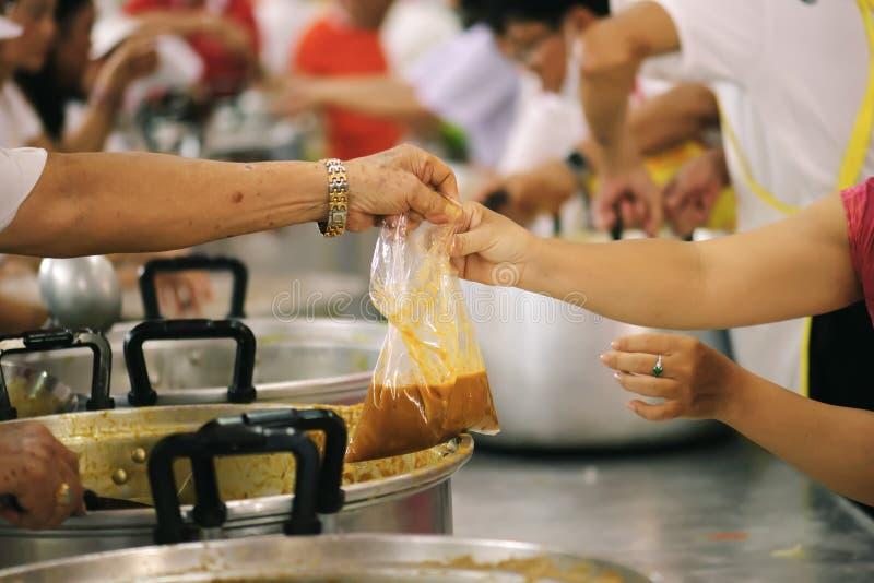 Προσφέρεται εθελοντικά τα τρόφιμα μεριδίου στους φτωχούς για να ανακουφίσει την πείνα: Έννοια φιλανθρωπίας στοκ εικόνες