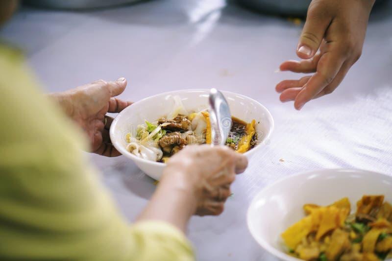 Προσφέρεται εθελοντικά τα τρόφιμα μεριδίου στους φτωχούς για να ανακουφίσει την πείνα: Έννοια φιλανθρωπίας στοκ εικόνα με δικαίωμα ελεύθερης χρήσης