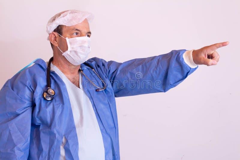 Προσφέρων ιατρικές υπηρεσίες με τη στολή του σε ένα ουδέτερο υπόβαθρο στοκ εικόνες