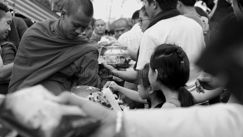 Προσφορές στο κύπελλο ελεημοσυνών ενός μοναχού στοκ εικόνα