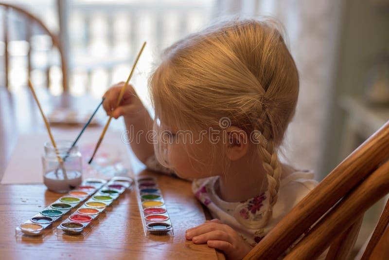 Προσχολικό ηλικίας κορίτσι με την ξανθή ζωγραφική τρίχας στην ετικέττα κουζινών στοκ φωτογραφίες
