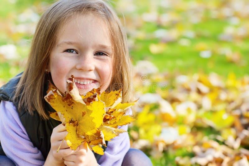 Προσχολικό κορίτσι με τα κίτρινα φύλλα στοκ εικόνες με δικαίωμα ελεύθερης χρήσης