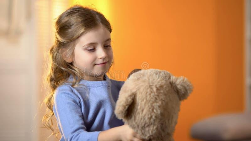 Προσχολικό κορίτσι που εξετάζει τη teddy αρκούδα, που παίζει με το παιχνίδι, ευτυχές λίγη πριγκήπισσα στοκ εικόνες