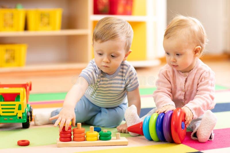 Προσχολικό παιχνίδι αγοριών και κοριτσιών στο πάτωμα με τα εκπαιδευτικά παιχνίδια Παιδιά στο σπίτι ή φύλαξη στοκ εικόνες με δικαίωμα ελεύθερης χρήσης