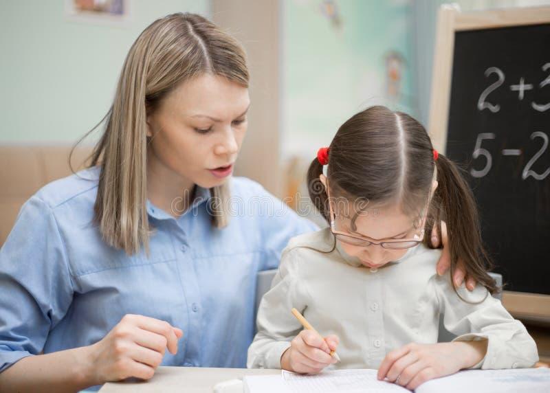 Προσχολική εγχώρια εκπαίδευση Το όμορφο νέο κορίτσι διδάσκει στο χ στοκ εικόνες