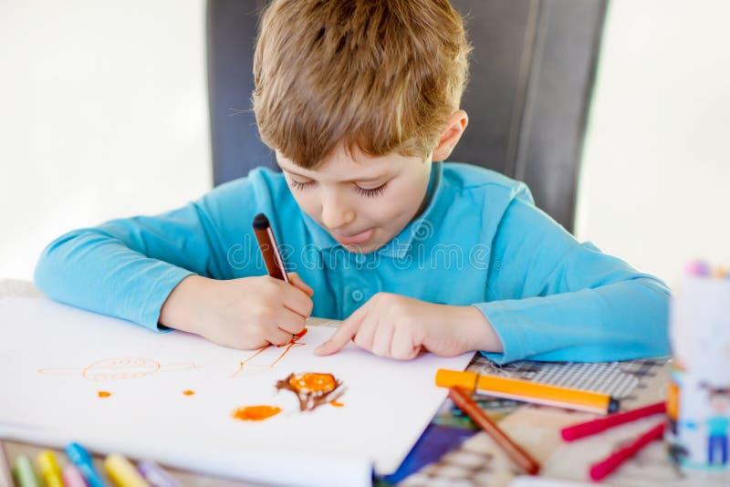 Προσχολικό αγόρι παιδιών που κάνει στο σπίτι την εργασία, που χρωματίζει μια ιστορία με τις ζωηρόχρωμες μάνδρες στοκ εικόνα με δικαίωμα ελεύθερης χρήσης