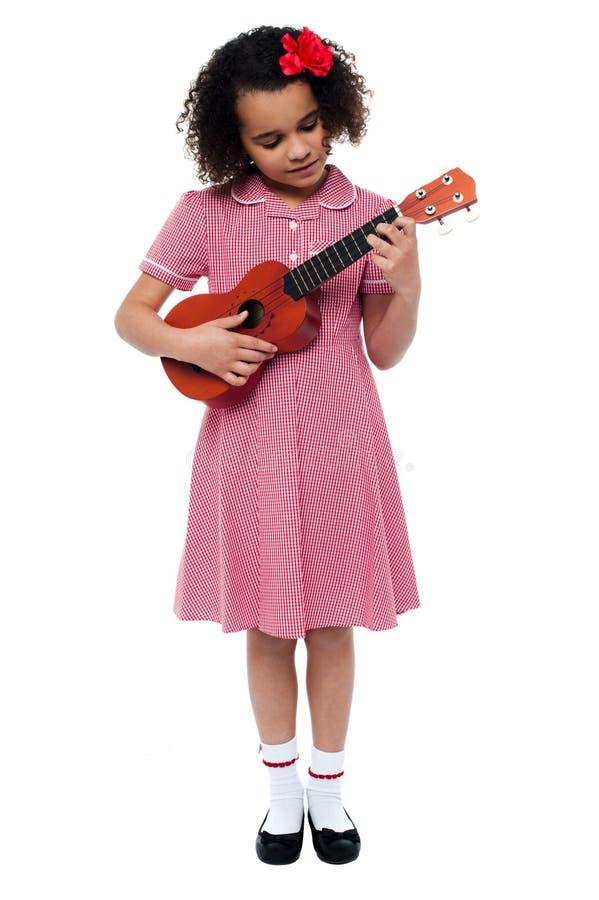 Προσχολικό χαριτωμένο κορίτσι που παίζει μια κιθάρα στοκ εικόνες με δικαίωμα ελεύθερης χρήσης