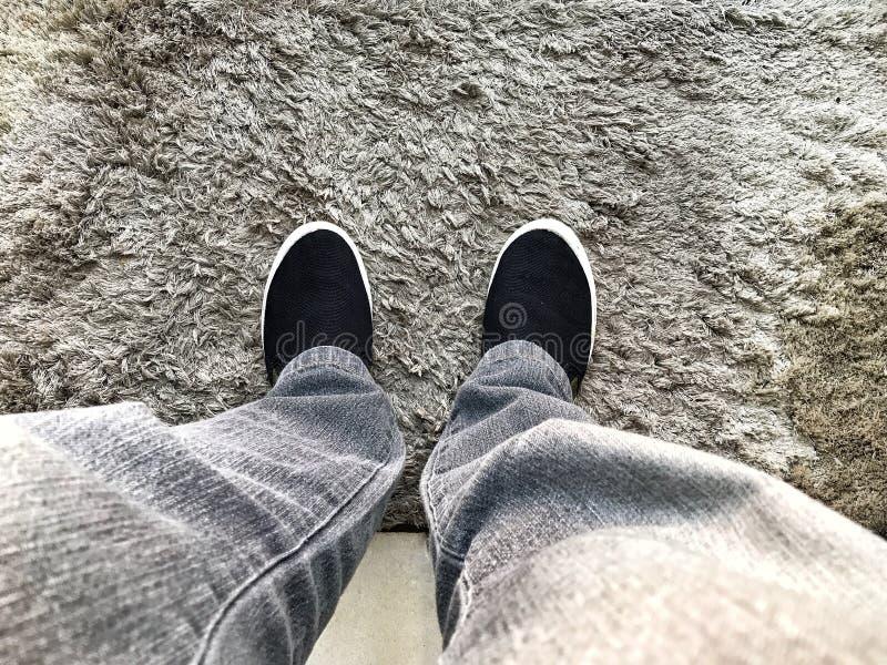 Προσωπική προοπτική των ποδιών σε έναν γκρίζο και γούνινο τάπητα στοκ εικόνα με δικαίωμα ελεύθερης χρήσης