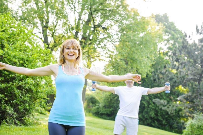Προσωπικός εκπαιδευτής με την άσκηση πελατών έξω στοκ φωτογραφία με δικαίωμα ελεύθερης χρήσης