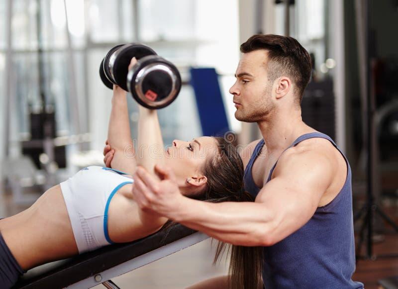 Προσωπικός εκπαιδευτής που βοηθά τη γυναίκα στη γυμναστική στοκ εικόνες