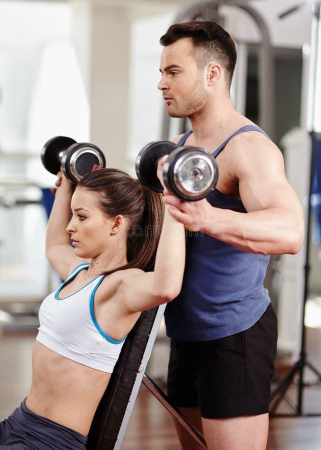 Προσωπικός εκπαιδευτής που βοηθά τη γυναίκα στη γυμναστική στοκ εικόνα