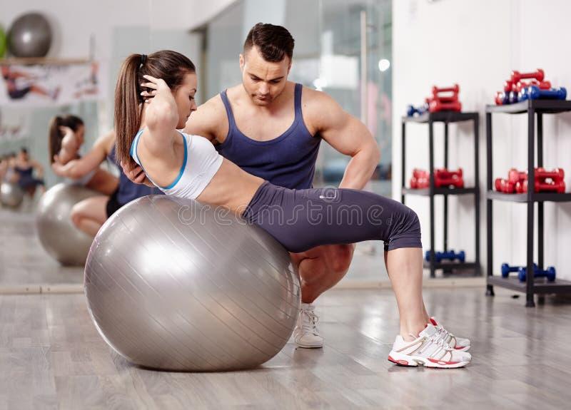 Προσωπικός εκπαιδευτής που βοηθά τη γυναίκα στη γυμναστική στοκ φωτογραφία