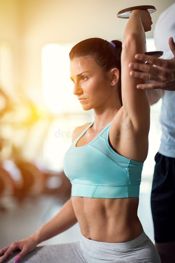 Προσωπικός εκπαιδευτής που βοηθά τη νέα γυναίκα στη γυμναστική στοκ φωτογραφία