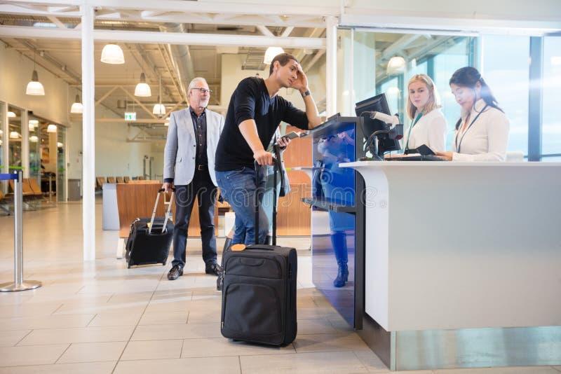 Προσωπικό που ελέγχει το διαβατήριο του αρσενικού επιβάτη στο μετρητή στον αερολιμένα στοκ εικόνα