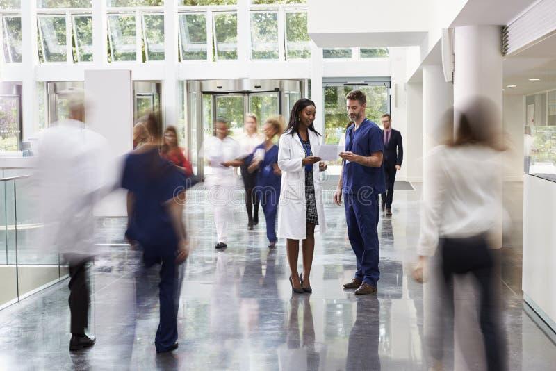 Προσωπικό στην πολυάσχολη περιοχή λόμπι του σύγχρονου νοσοκομείου στοκ εικόνα με δικαίωμα ελεύθερης χρήσης